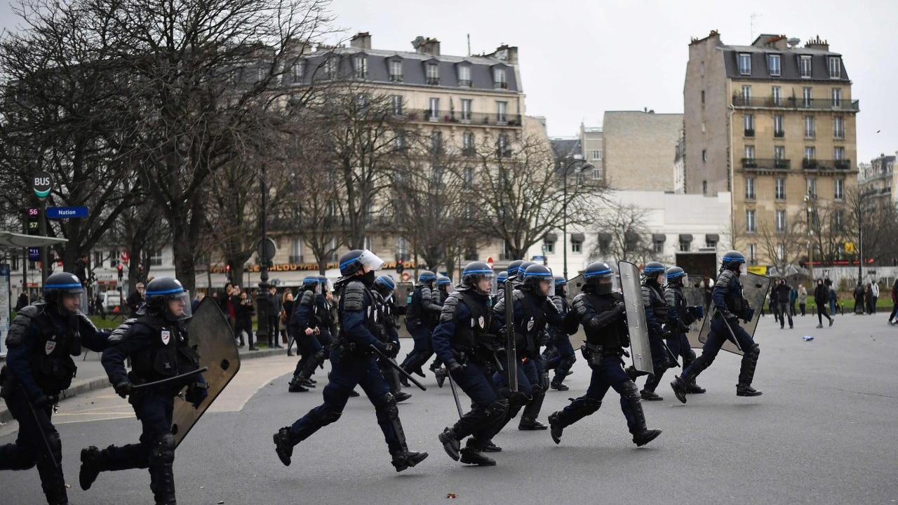 TOPSHOT - Members of the riot police charge at demonstrators during a protest of students against police brutality, following the alleged rape of Theo in Paris, on February 23, 2017. / AFP PHOTO / Lionel BONAVENTURE
