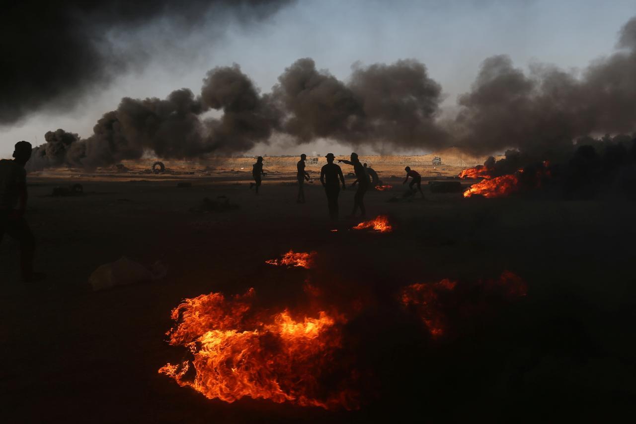 Palestiinlased põletavad rehve, et suitsu varjus piirile pääseda.